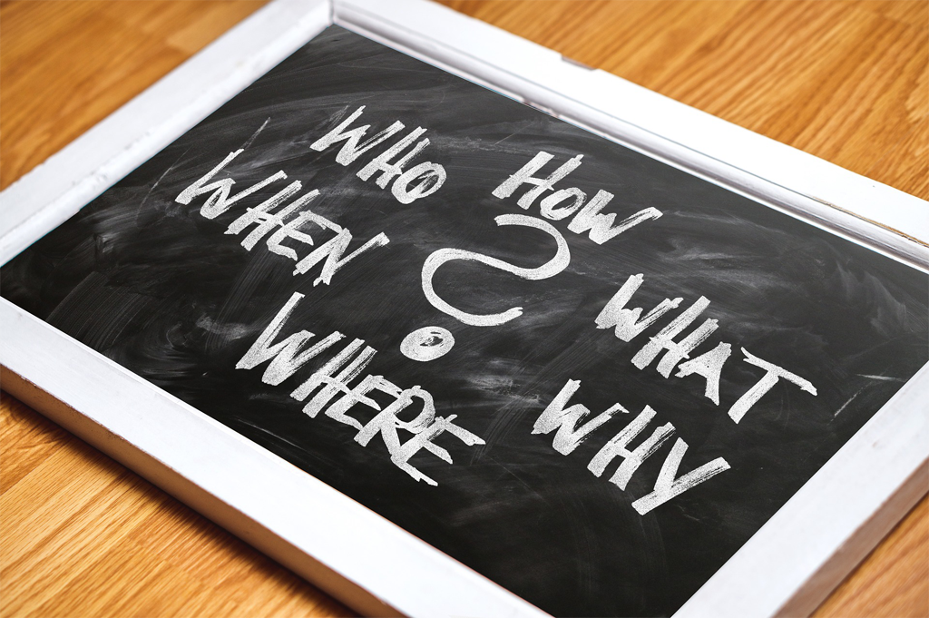 """Blackboard with the words """"How, What, Why, Where, When Who"""" written on it."""