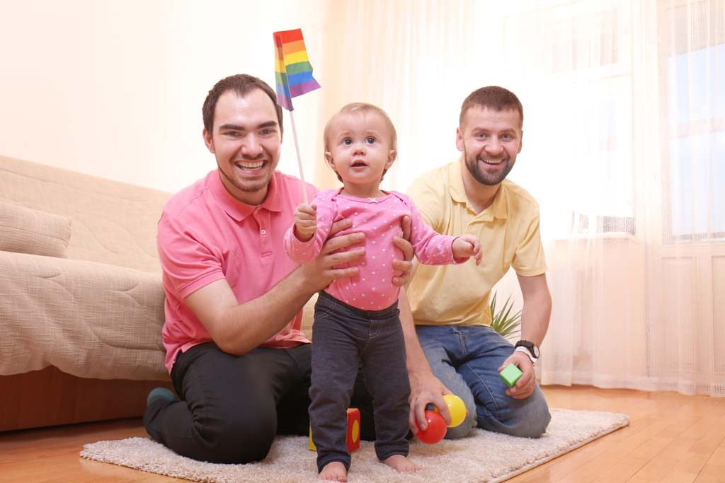 Two same-sex parents with their child, holding a rainbow pride flag.